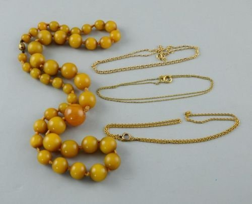 Four necklaces comprising three gold chains and an ambe