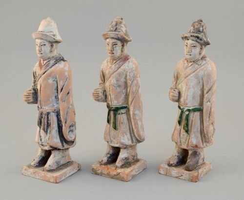 Three Chinese pottery standing figures, grooms wearing