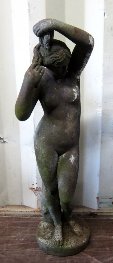 Composite stone figure of a nude woman standing in a cl