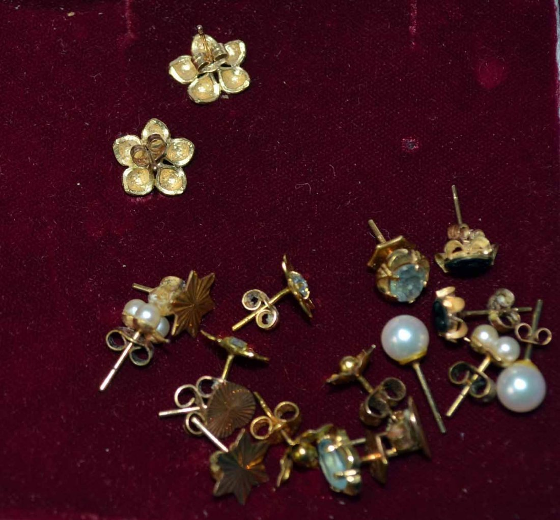 Nine pairs of 9ct gold earrings, mainly floral settings