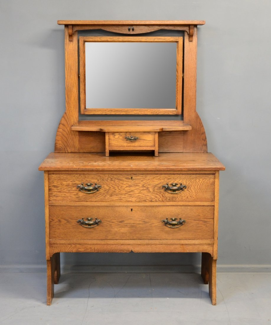 An early 20th Century oak dressing chest pierced frame