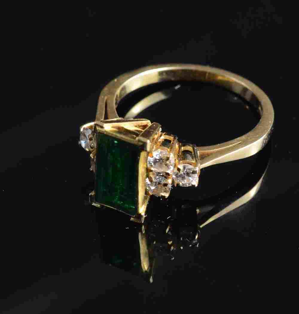 An Emerald and diamond ring set in 18ct gold table cut