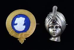 A brooch in the form of a boys head with garnet set