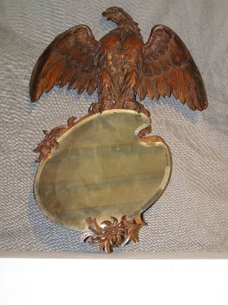 28: Continental walnut carved wall mirror, the finial i