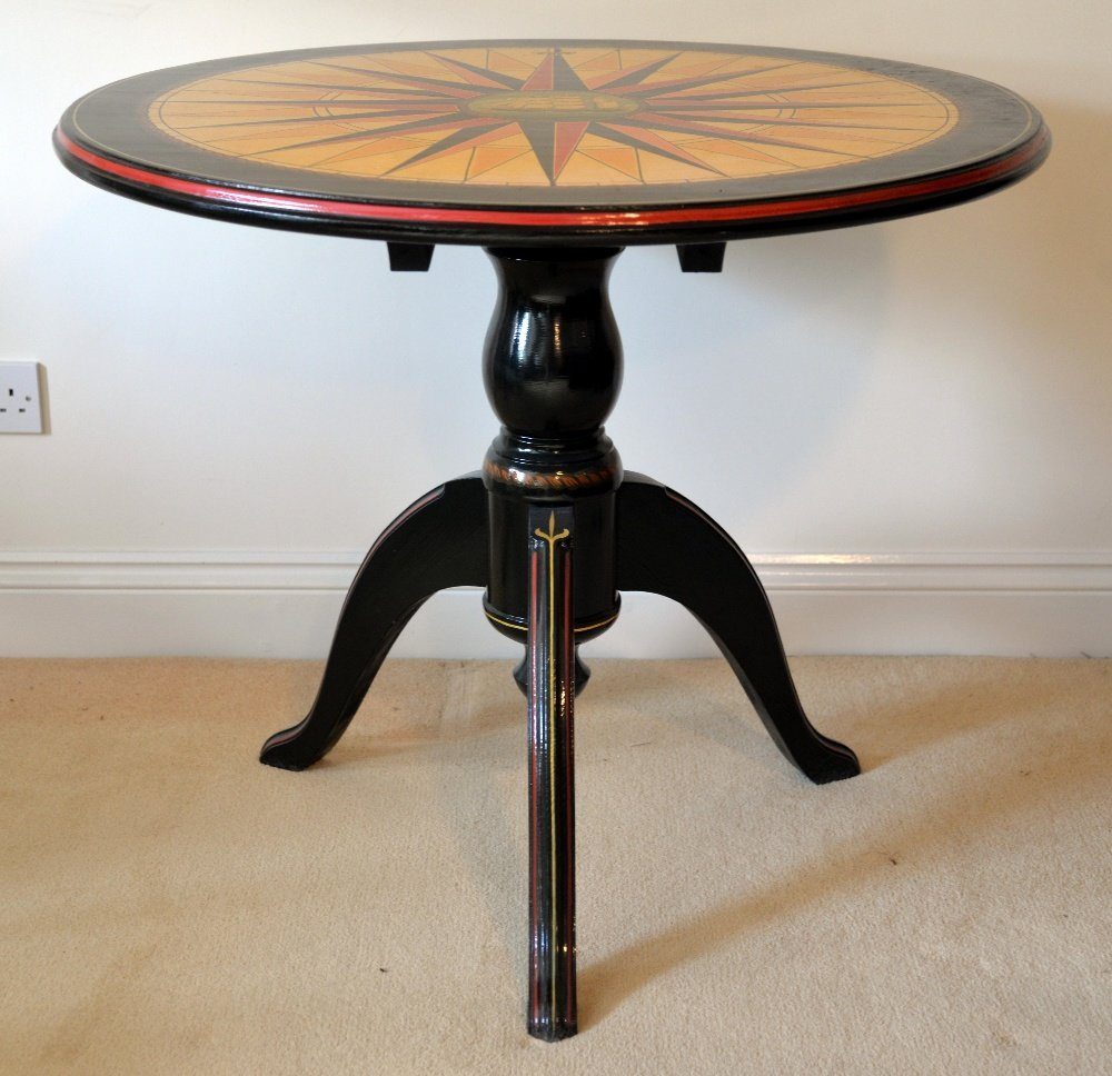 Black, red and gilt decorated tripod table,