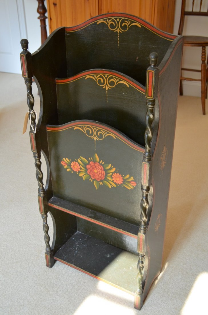 Black, red and gilt painted magazine rack,