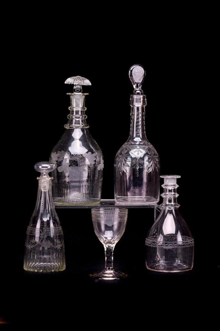 4 GEORGE III ENGRAVED OR CUT DECANTERS & A WINE GLASS