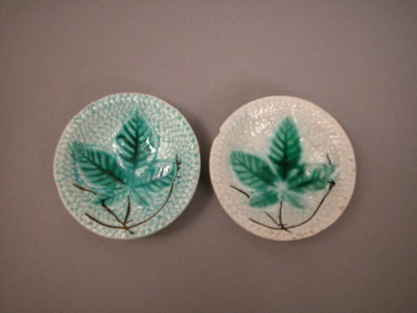 413: Majolica Pair of round butter pats with leaves on