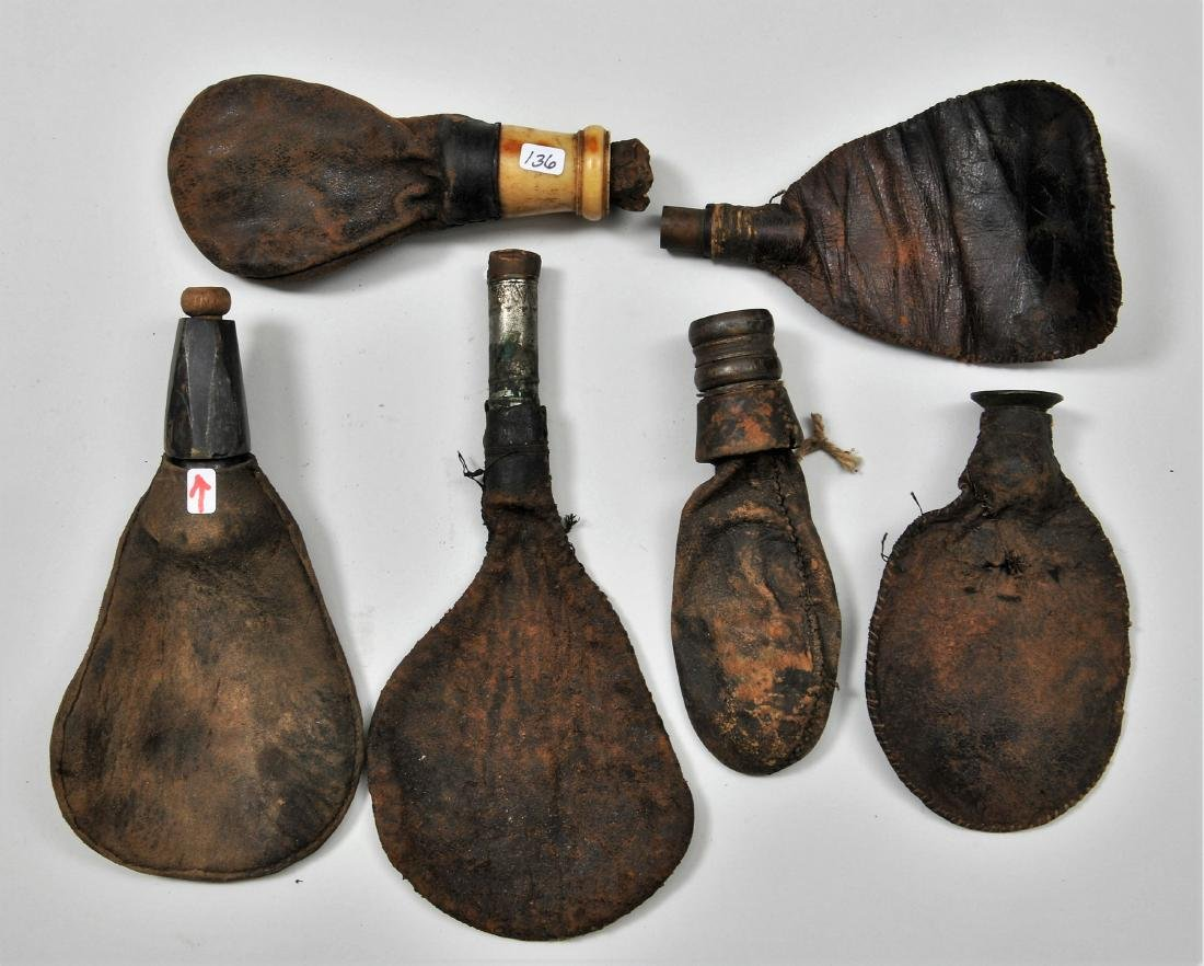 Lot of six early leather shot bags with applied spouts.