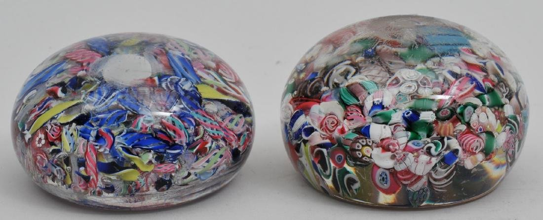 Two scrambled glass paperweights. Both with large air