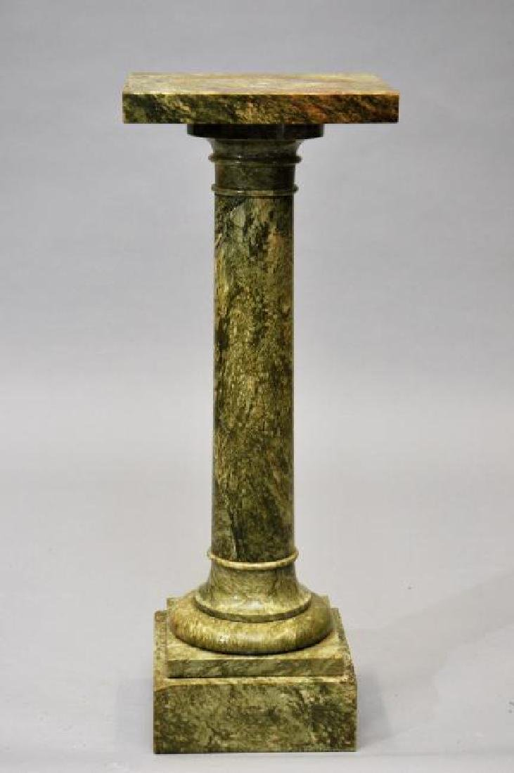 Green marble pedestal with round column and square top.