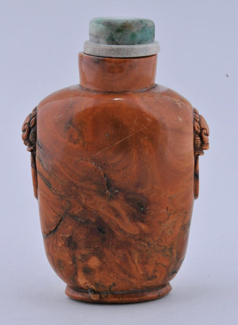 Root amber Snuff bottle. China. 19th century. Lion mask