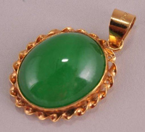 Jade cabochon pendant with 18 karat gold setting.  Jade