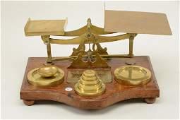 Edwardian brass postal scale mounted on an oak base