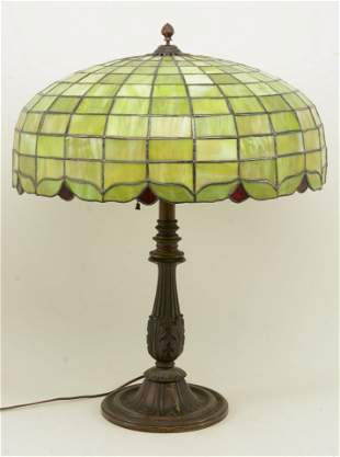 Leaded glass table lamp with cast base circa 1920. The