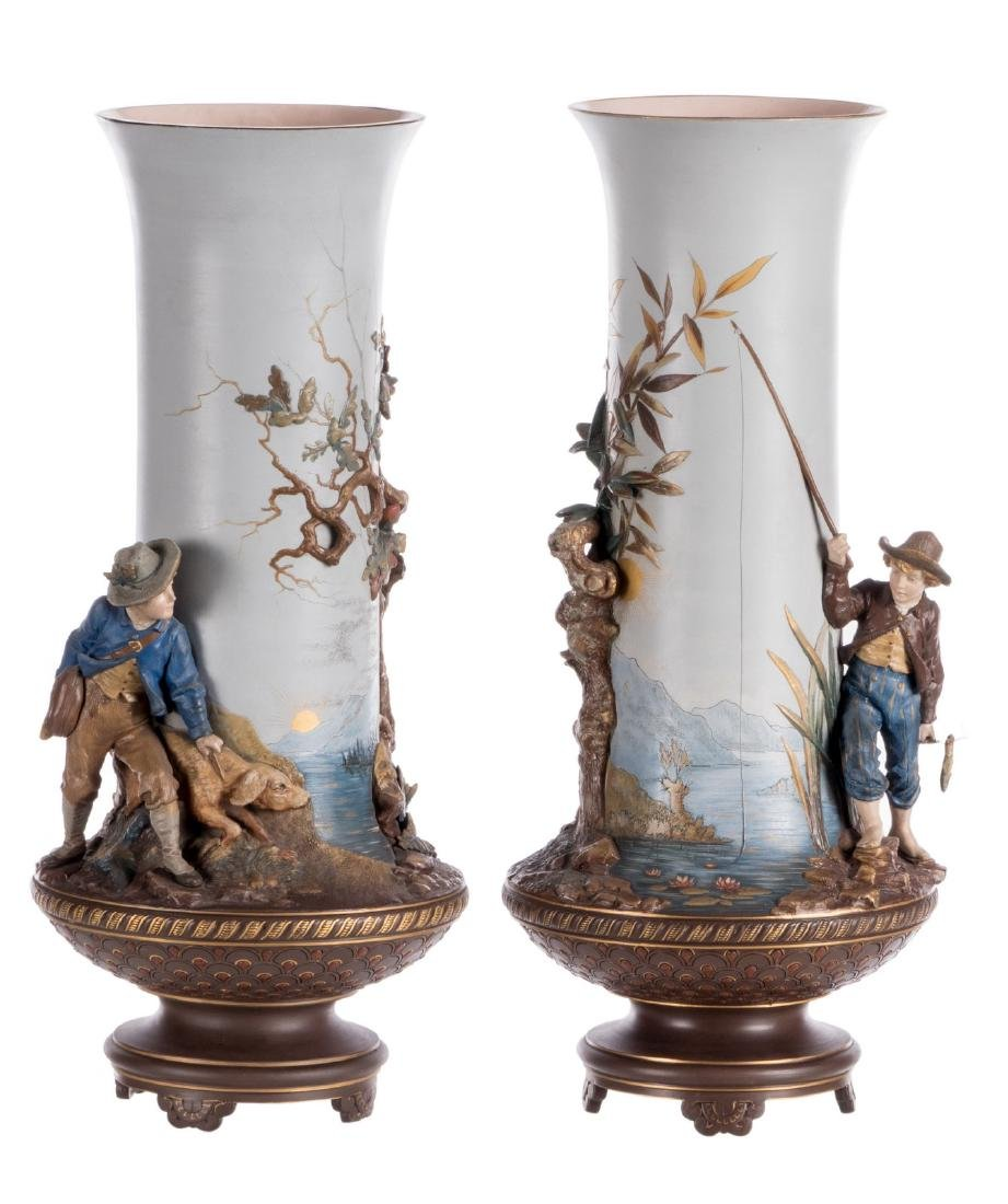 A pair of red stoneware vases, polychrome and partly