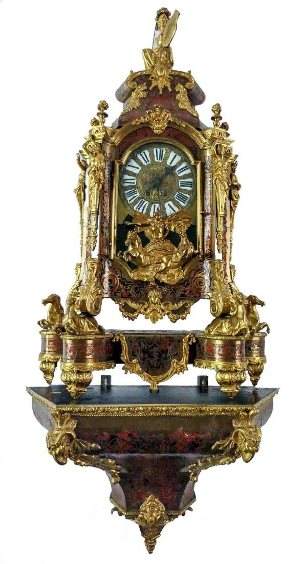 A cartel clock with accompanying base in Louis