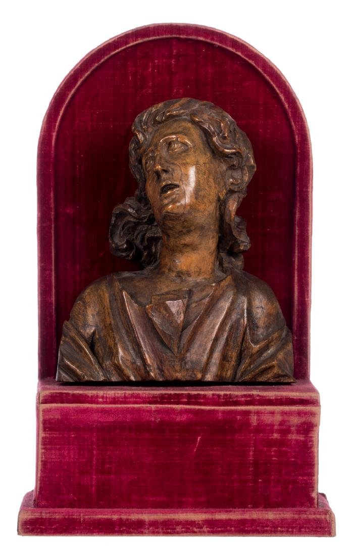 A wooden bust of Saint John the Baptist on a red velvet