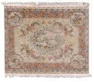 An Oriental silk rug with floral motifs the roundels