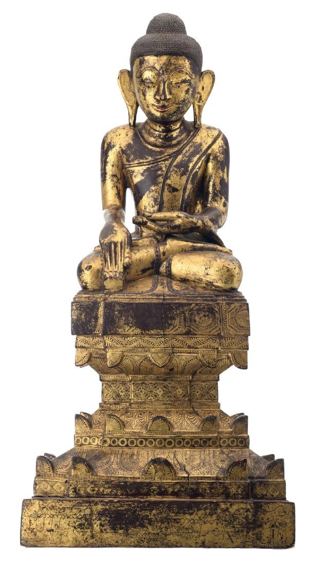 A Burmese gilt lacquered wooden seated Buddha, on lotus