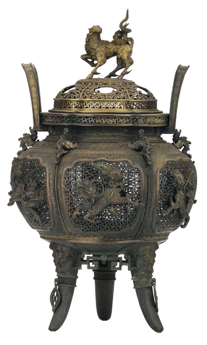 A Chinese open work and relief decorated bronze tripod