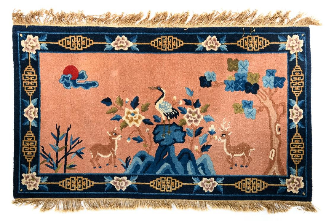A Chinese carpet decorated with a crane and deer in a