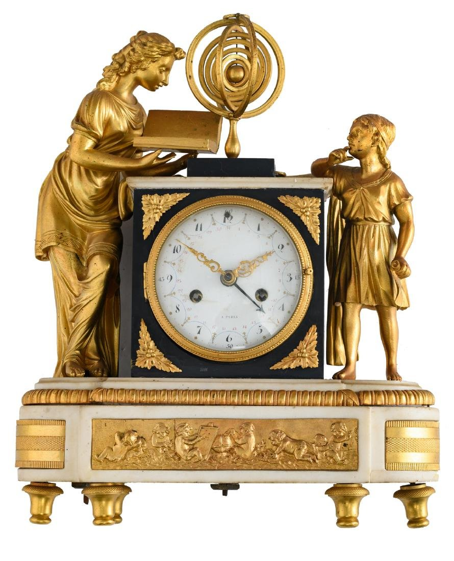 A gilt bronze mantle clock on a white Carrara marble