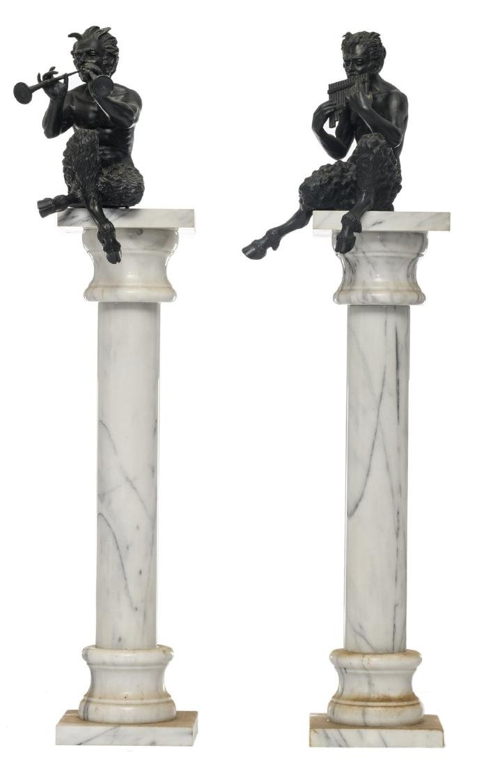 A pair of cast iron music making satyrs on a white and