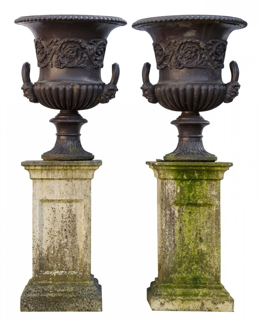 A pair of patinated cast iron Medici garden vases on