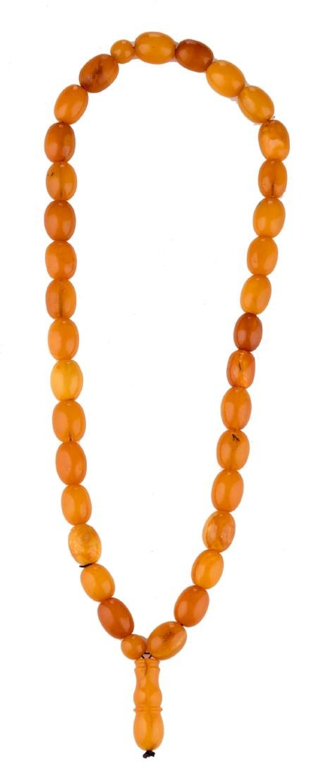 A Chinese Buddhistic amber pearl necklace, H 28 - ø 18