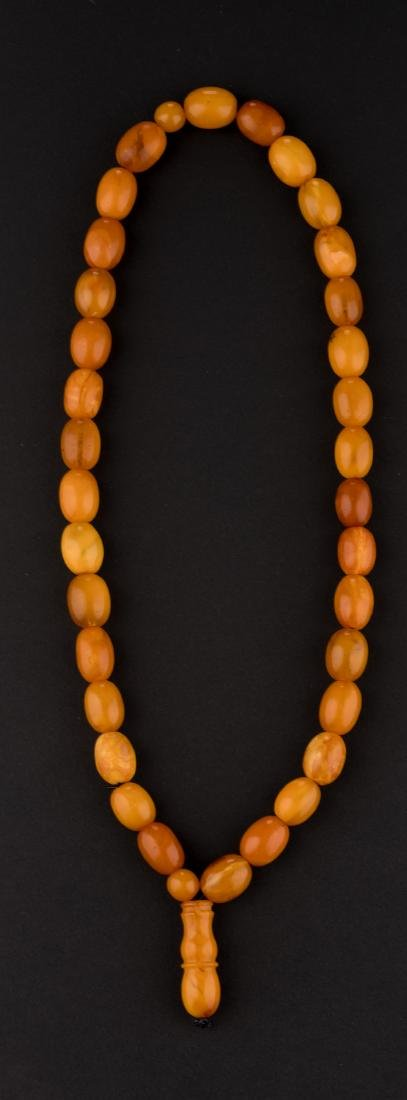 A Chinese Buddhistic amber pearl necklace, H 28 - ø 18 - 3