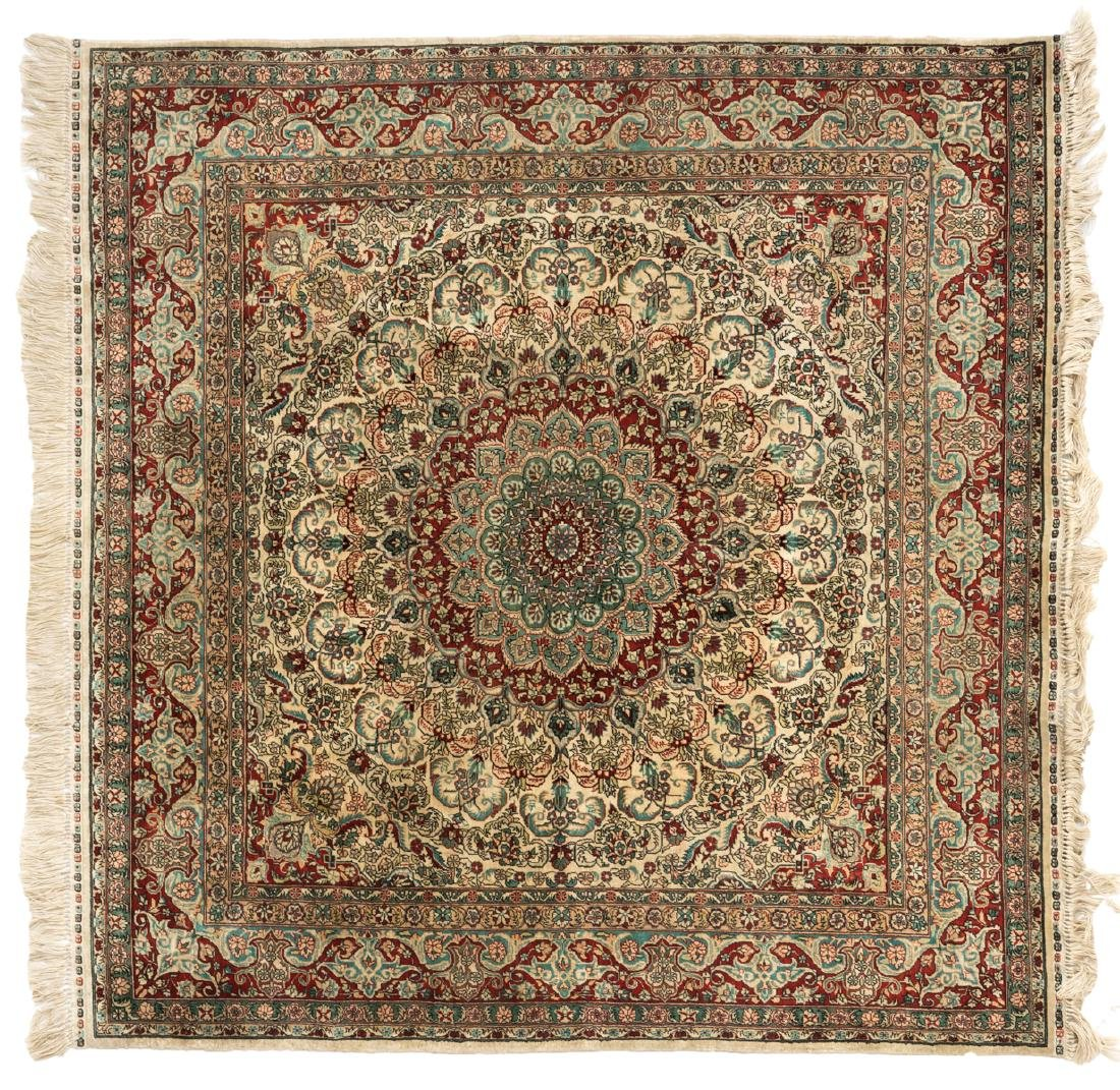 An Oriental square silk carpet with floral motifs and