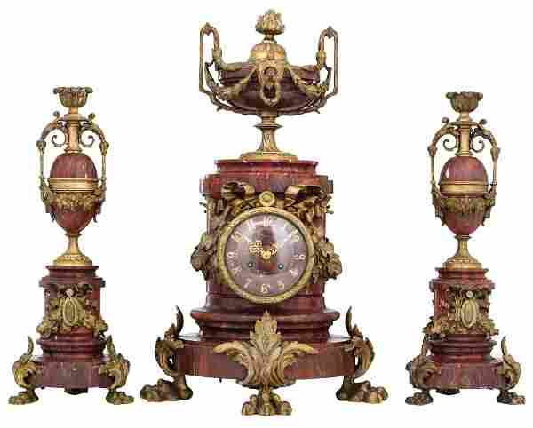 A three-piece rouge Napoleon marble garniture,