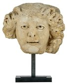 A sandstone head fragment of a man, on a metal stand,