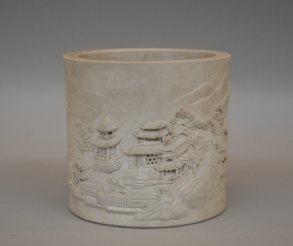 A Chinese biscuit porcelain brush pot decorated with a