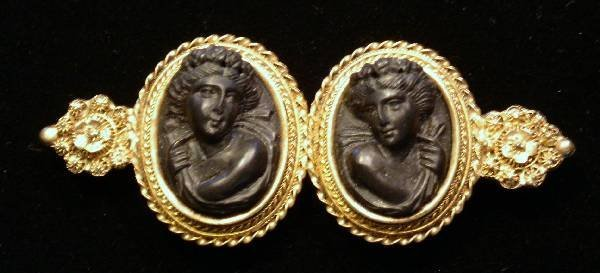 41: Gold pin with two carved black lava relief figures