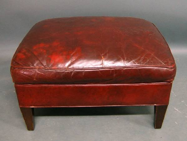 259: Red leather chair and footstool.