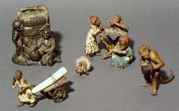 15: Four Austrian cold painted bronze figures and a Cot