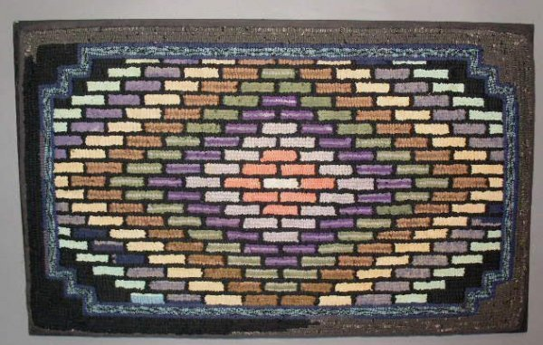 24: Hooked rug with colorful brick pattern, mounted for