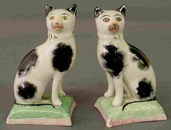 Two small 19th c. Staffordshire cats seated on gre