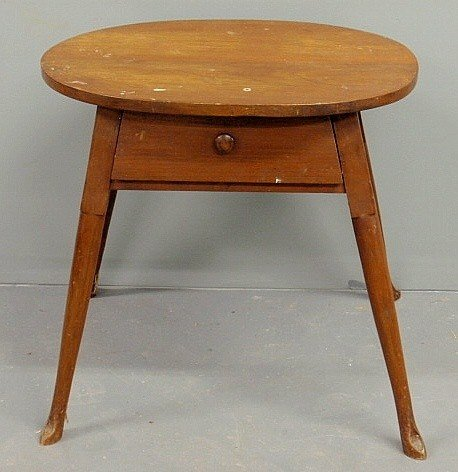 185: Walnut oval top tavern table, 20th c., with a sin