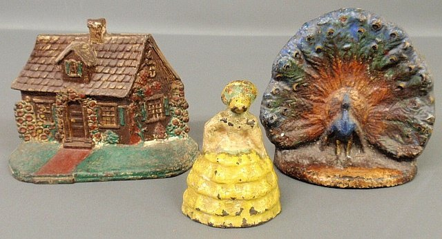Three Victorian cast iron doorstops, log cabin, woman w