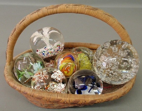 Nine 20th c. glass paperweights in a basket, largest