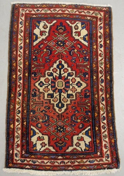 Persian oriental mat with a red field and center