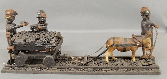 Folk art carving of coal miners, donkey and cart on