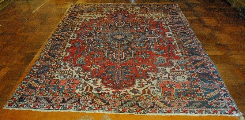 Room size Heriz oriental carpet with red field.