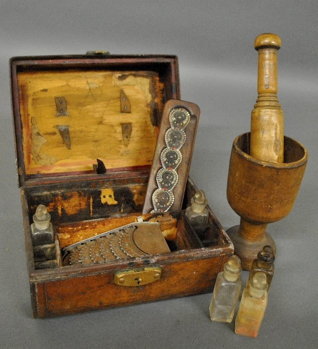 Leather cased medical box with a wood mortar and
