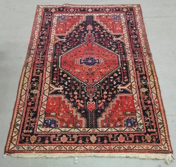 Oriental center hall carpet with red field. 8' x 4'7""