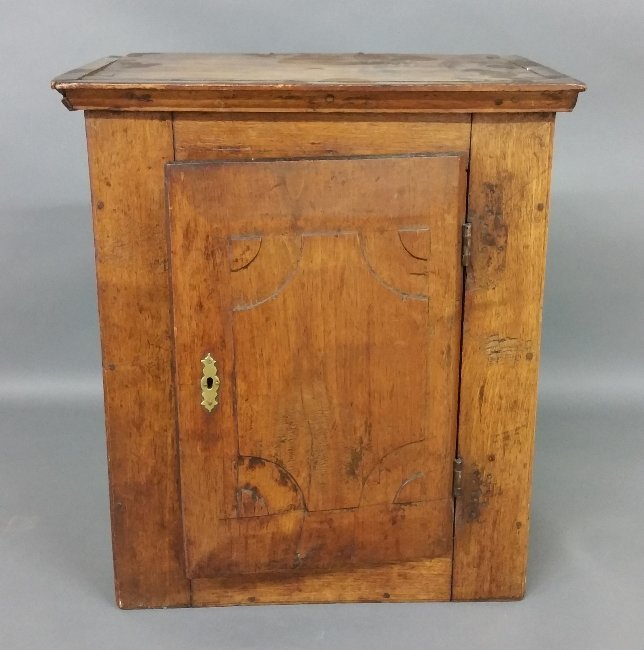 Walnut hanging cupboard with a carved door, 18th