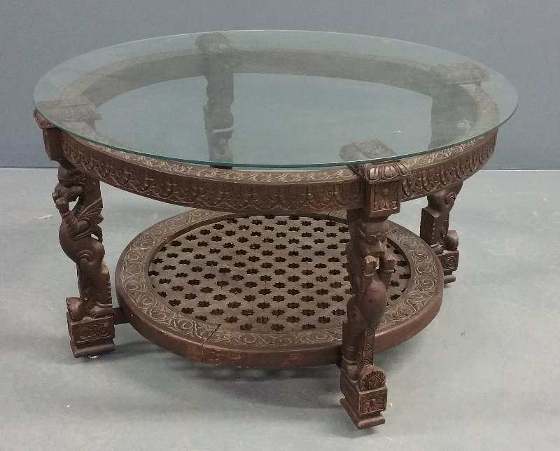 A fine carved circular African table with a glass top